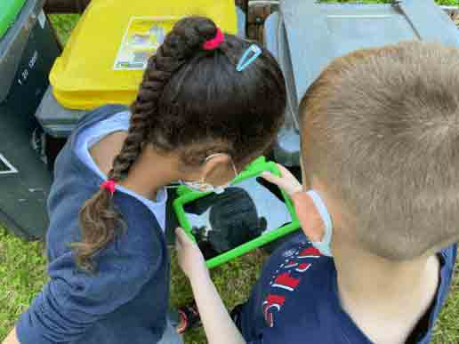 Deux enfants qui découvrent le jardin avec la tablette